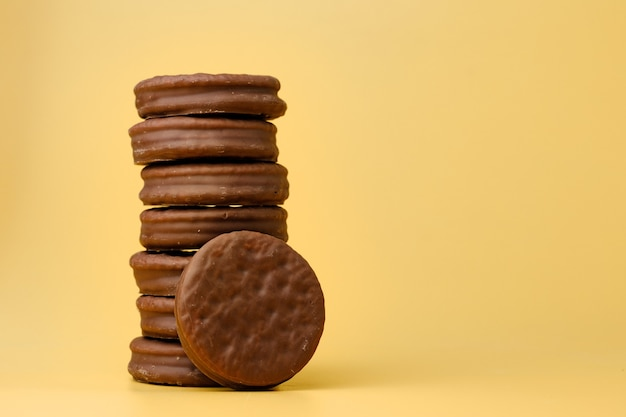 Stack of chocolate cookies on yellow backgreound front view
