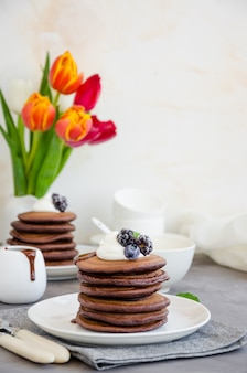 Stack of chocolate pancakes on a white plate with chocolate sauce, whipped cream, blueberries and blackberries on top of a concrete background.