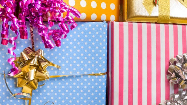 Stack of christmas or birthday present in colorful wrapping paper decorated with ribbons and bows