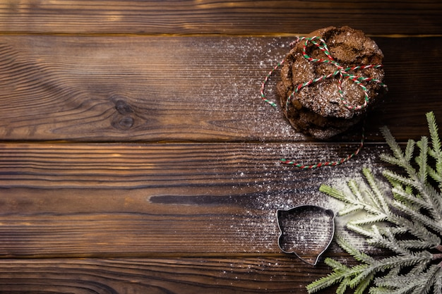Stack of christmas chocolate cookies tied with striped rope on textured wooden table sprinkled with flour