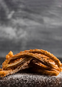 Stack of churros with sugar and copy space
