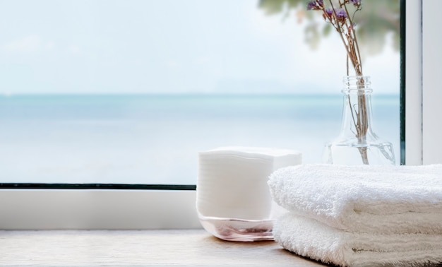 Stack of clean bath towels on wooden table near the window with seascape. copy space.