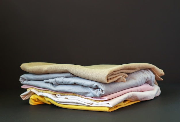Stack of clean bedding sheets. natural linen colorful fabrics on dark background.