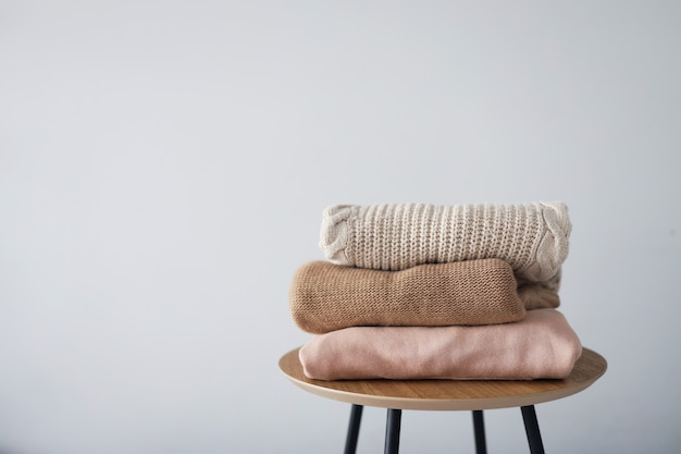 Stack of clean freshly laundered, neatly folded women's clothes on wooden table. warm autumn sweaters.