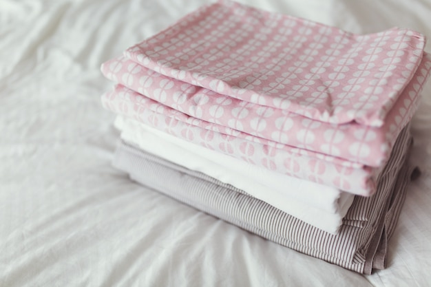 A stack of clean and ironed linen is on the bed