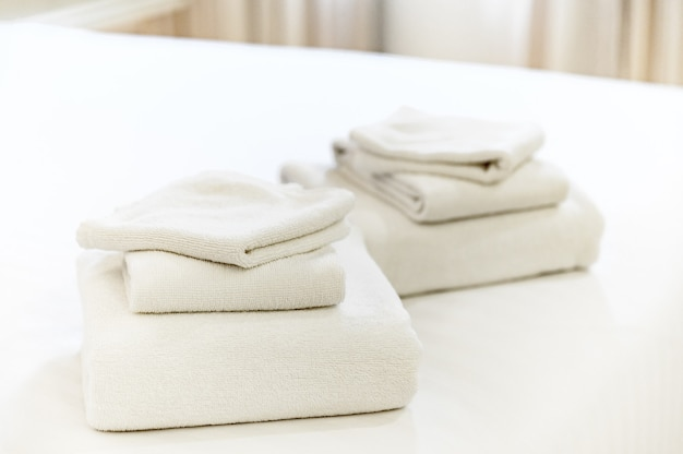 Stack of clean towels on bed in hotel.