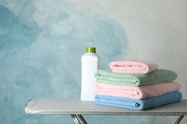 Stack of clean towels and laundry liquid on ironing board,