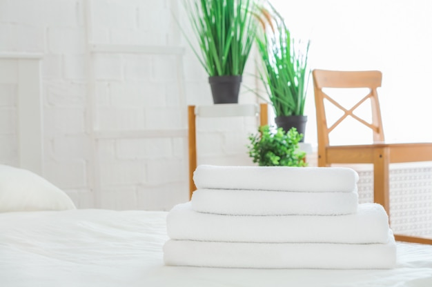 Stack of clean towels on white bed in room. space for text.