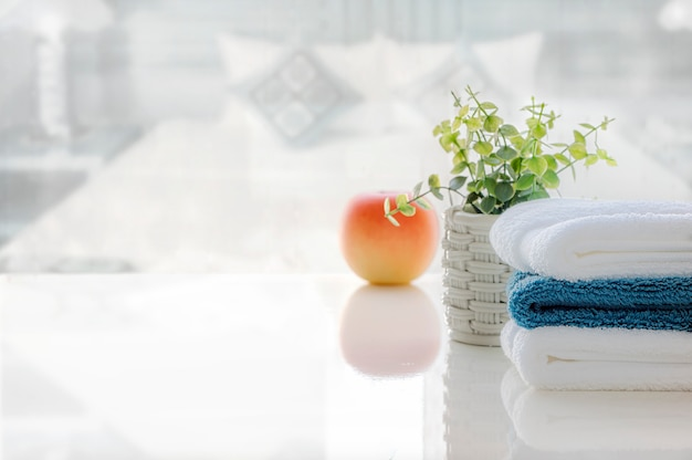 Stack of clean towels on white table with blur of bed room, copy space for product display.