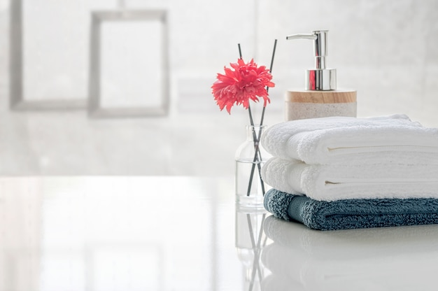 Stack of clean towels on white table with blur of living room, copy space for product display.