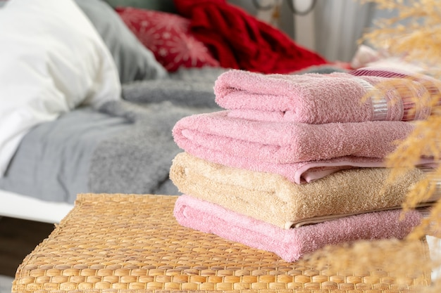 Stack of clean towels on wooden table in bedroom