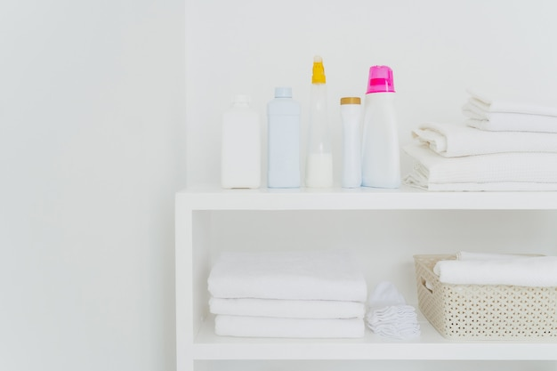 Stack of clean white towels with detergents on console isolated. fresh laundry and liquid washing in bathroom