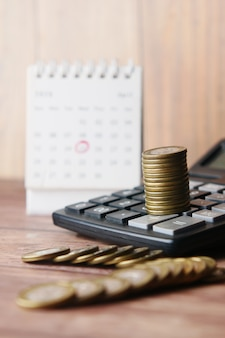 Stack of coins  calculator and calendar on table
