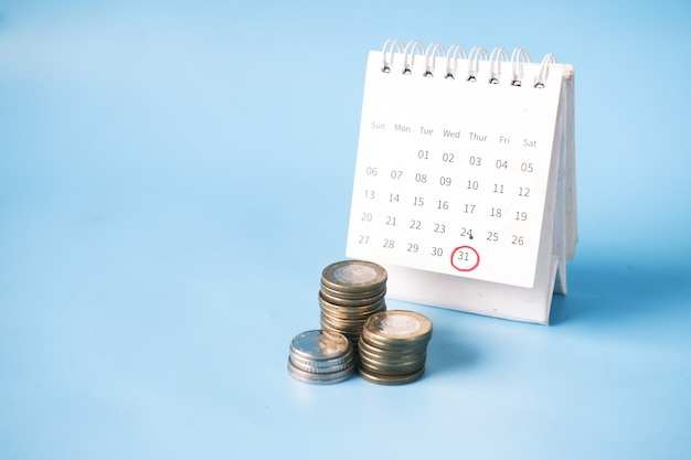 Stack of coins and calendar on blue background .