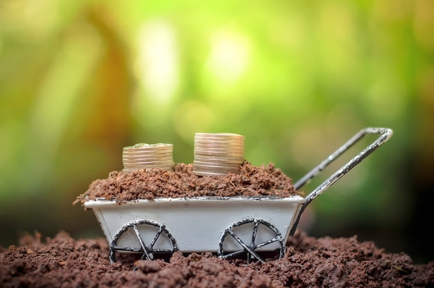 Stack of coins growing up on wheel barrow for business investment or saving concept