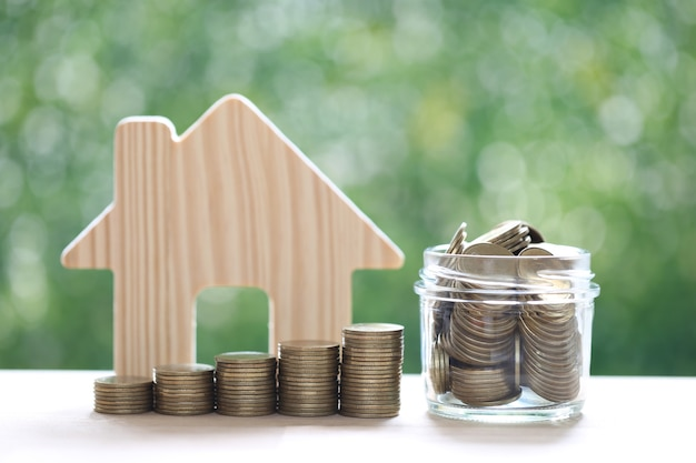 Stack of coins money in the glass bottle and model house on natural green background,saving for prepare in future and business investment concept