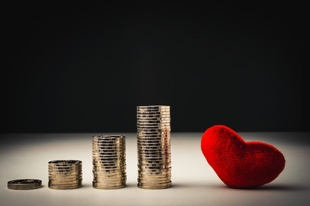 Stack of coins and red heart