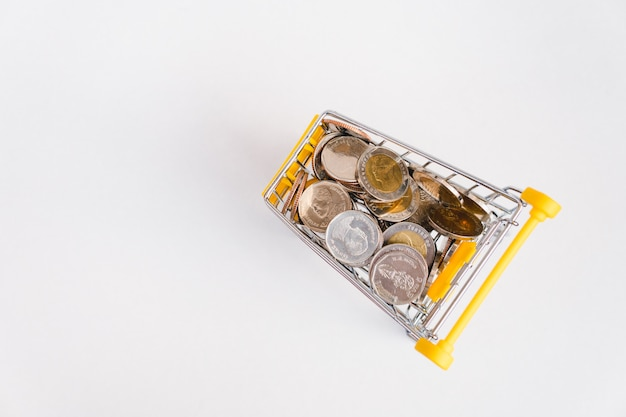 Stack coins in shopping cart on white background
