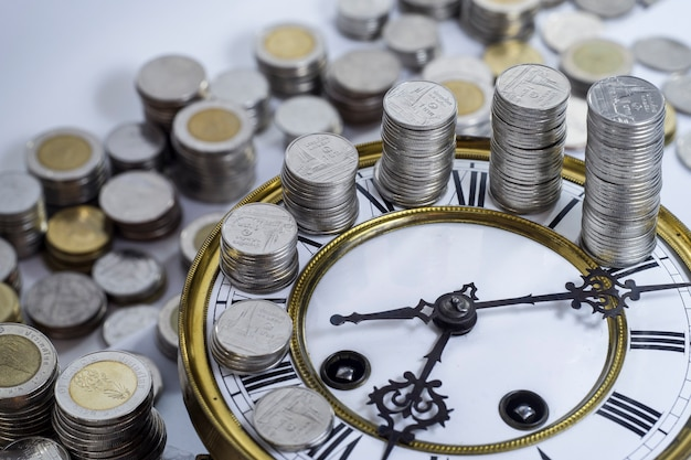 Stack of coins on vintage clock