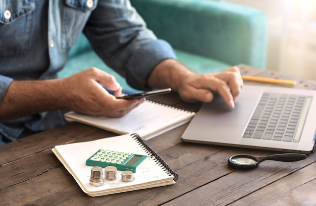 Stack of coins with a calculator on a wooden table. man examining home finance or starting new business concept