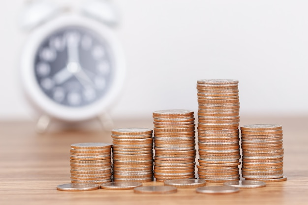 Stack of coins with clock for saving money concept