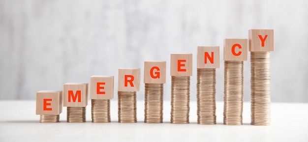 Stack of coins with emergency text.