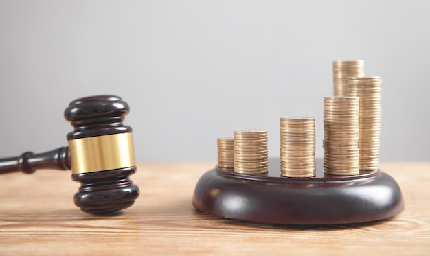Stack of coins with judge gavel.