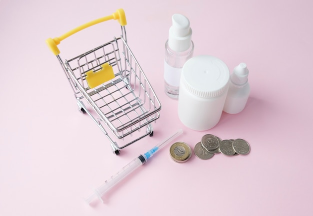 Stack of coins with medicine bottle on the pink background