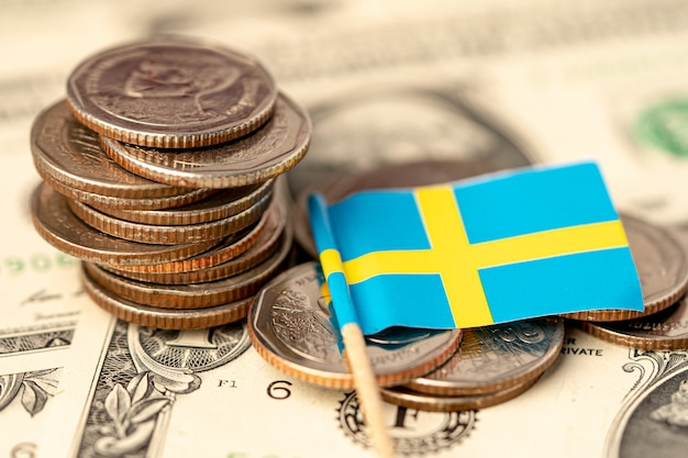 Stack of coins with sweden flag on usa america dollar banknotes.