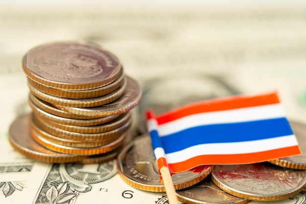 Stack of coins with thailand flag on usa america dollar banknotes.