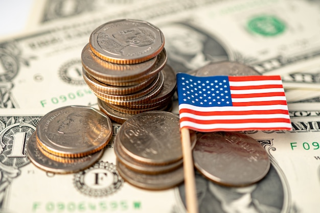 Stack of coins with usa america flag on dollar banknotes.