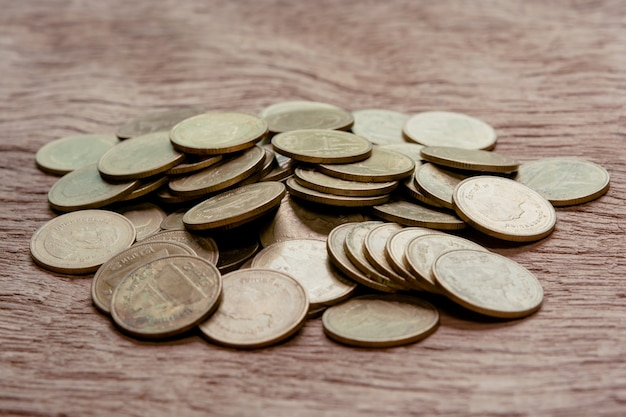 Stack coins on wood table.