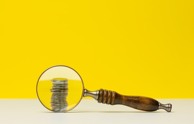Stack of coins and a wooden magnifier on a white table, yellow background. the concept of analysis of budget funds, control of expenditures and incomes. small salary, fundraising for a startup