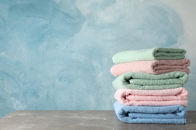 Stack of color towels on grey table on blue, space for text