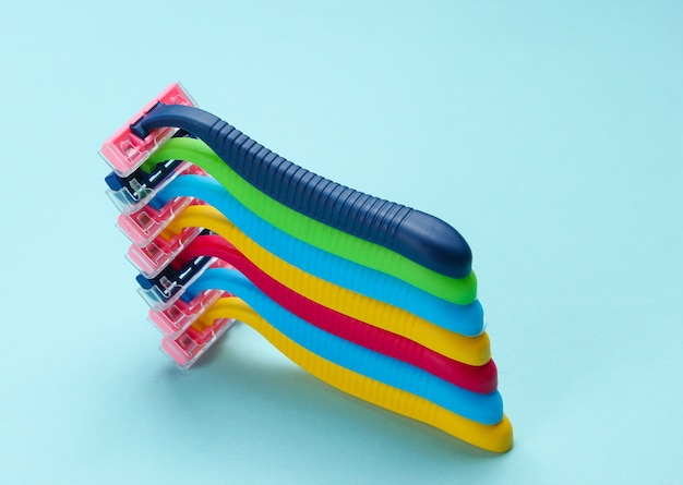 Stack of colored plastic razors on blue