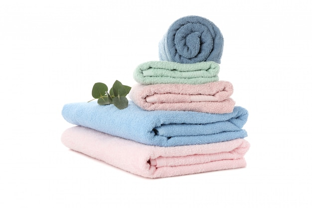 Stack of colored towels and eucalyptus isolated on white background