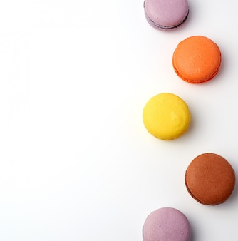 Stack of colorful baked macaronlmond flour on white