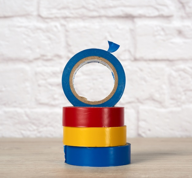 Stack of colorful insulating tape on white brick wall, close up
