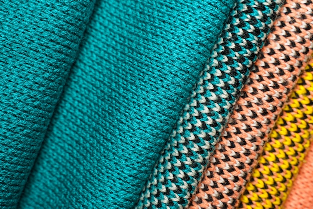 Stack of colorful knitted fabric, knitted winter clothes. multicolored knitwear fabric background