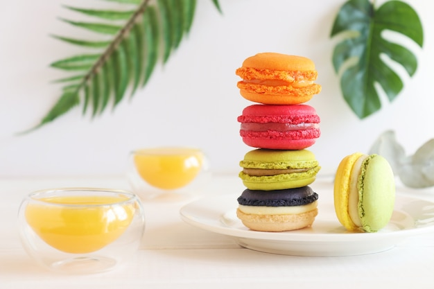 Stack of colorful macaroons on the table with two cups of orange juice and palm leaves as a decor