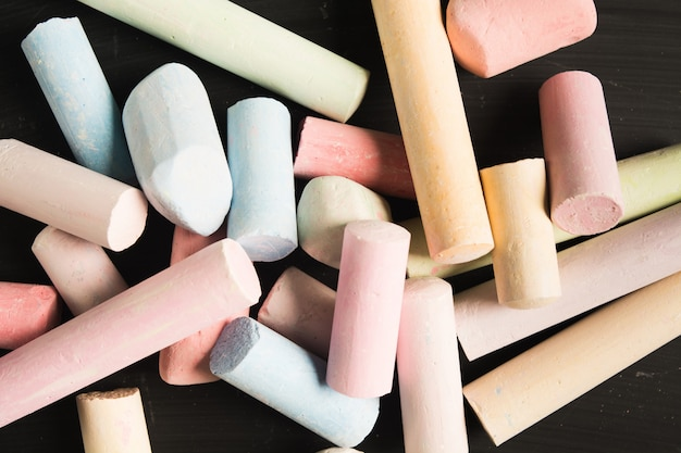 Stack of colorful pastel pieces of chalk over blackboard