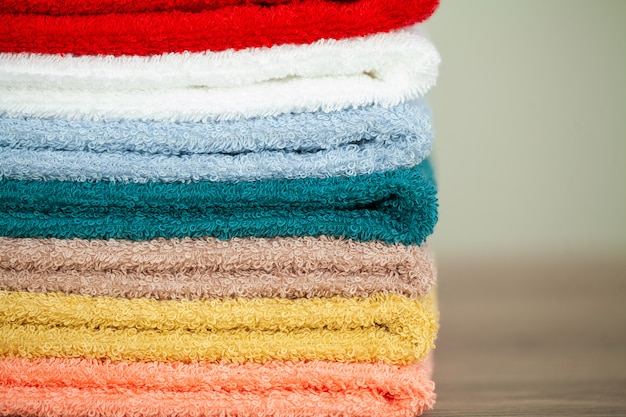 Stack colorful towels in bathroom on table