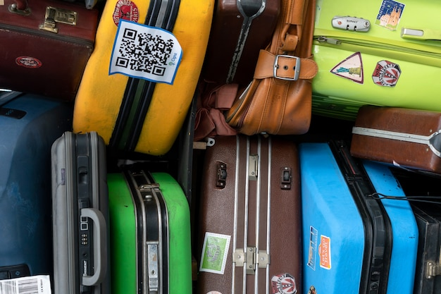 Stack of colorful travel suitcases at terminal airport