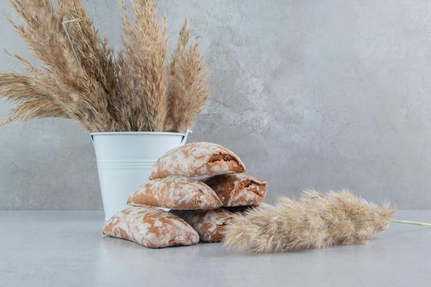 Pila di involucri di biscotti e fascio di gambi di erba piuma su sfondo di marmo.