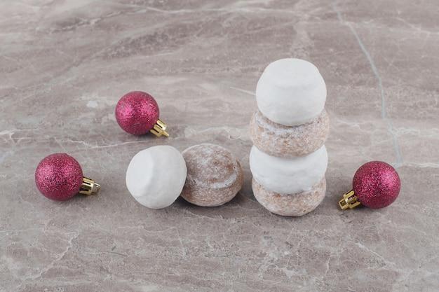 Una pila di biscotti e palline di natale impacchettate sul marmo