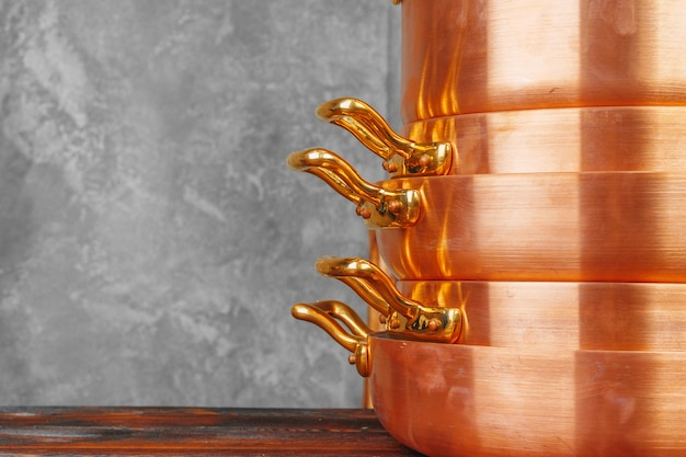 Stack of copper cooking pans on wooden table close up