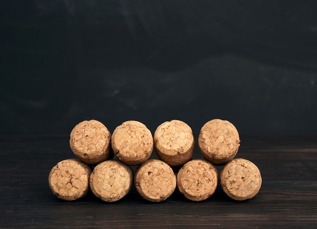 Stack of corks for glass wine and champagne bottles on wooden background