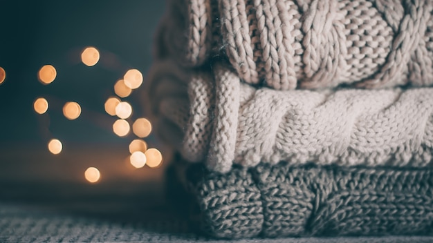 Stack of cozy knitted sweaters and garland lights on wooden background