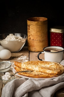 Stack of crepes and ingredients for cooking on a table