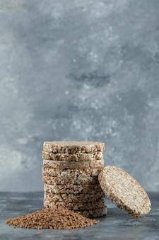 Pila di fette biscottate e mucchio di grano saraceno sulla superficie di marmo